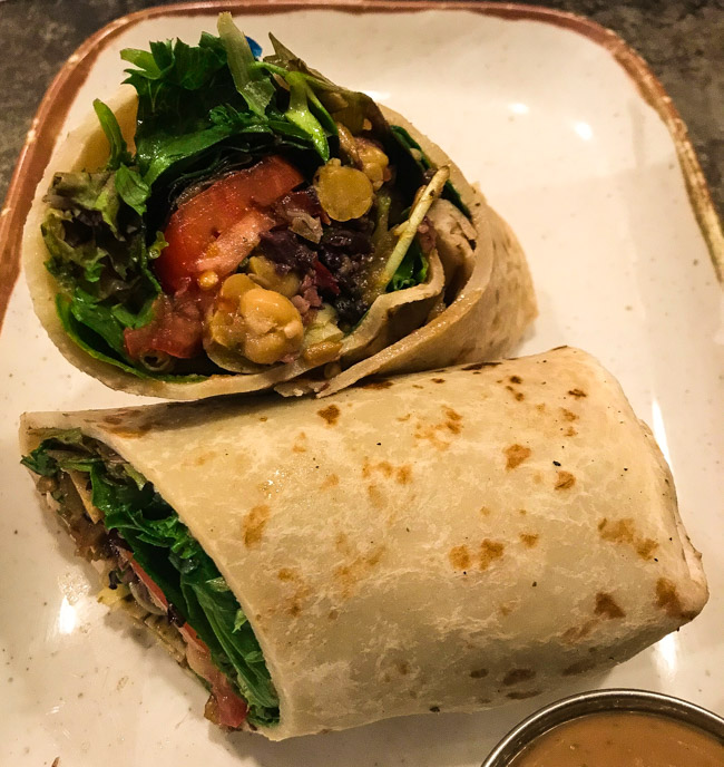 The Bella sandwich from Mudgie's Deli in Detroit, MI features tomato, chick peas, roasted red pepper, artichoke hearts, olive tapenade, sunflower sprouts, mixed greens, sunflower seeds, rolled up in a flatbread with a balsamic vinaigrette.