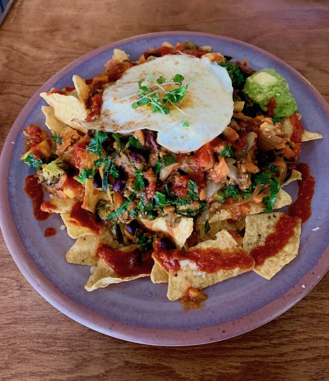 The Veggie Nachos from Juicy Kitchen in Ann Arbor are topped with sauteed kale, sweet potato, broccoli, black beans, salsa, guacamole, and a fried egg. Read the full review at www.thebite2night.com